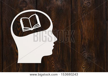 Paper head with book inside. Reading or knowledge concept. Abstract conceptual image with copyspace. Dark wooden background