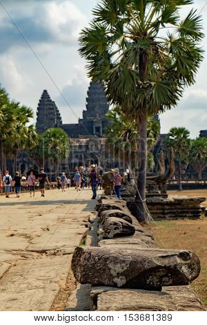 Ancient ruins of temple complex Angkor Wat surrounded by palm trees Siem Reap Cambodia. Selective focus on the rock in the foreground