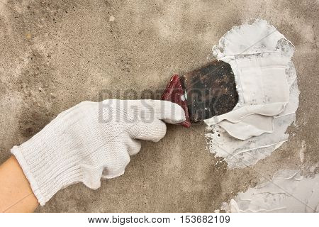 hand plastering concrete wall with spatula during repair