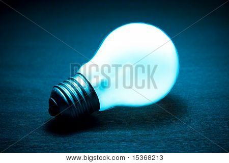 Glowing light bulb on a dark background. Blue tint.
