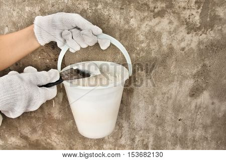 hands holding bucket with plaster and spatula on the concrete wall background