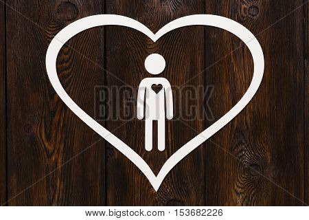 Paper man inside big heart on dark wooden background. Love relation concept. Abstract conceptual image
