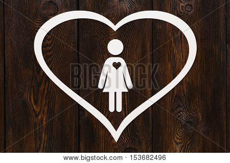 Paper woman inside big heart on dark wooden background. Love relation concept. Abstract conceptual image