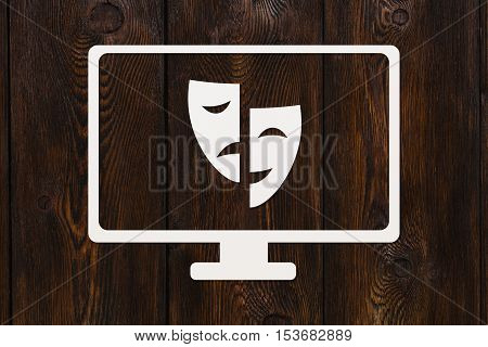 Paper tv with masks. Theatre vs movie. Abstract conceptual image on dark wooden background