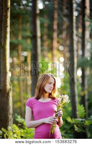 Outdoor portrait of beautiful pregnant woman on summer day