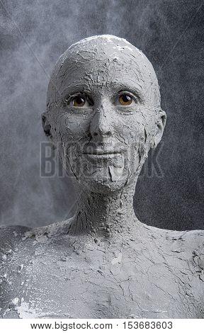 Statuesque woman in wet clay. Woman covered in wet clay. Spa treatment or scary Halloween mask?