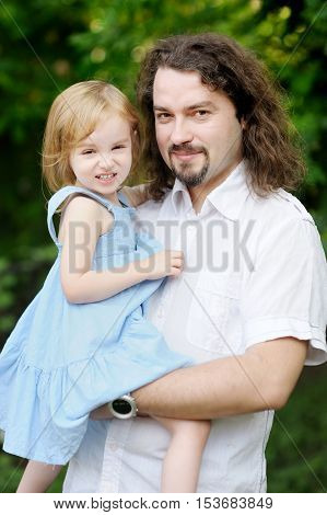 Young father and his adorable daughter on summer day