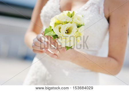 Bride holding beautiful white wedding bouquet on summer day