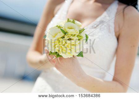 Bride holding beautiful white wedding bouquet on wedding day