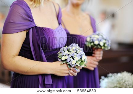 Row of bridesmaids with bouquets during wedding ceremony