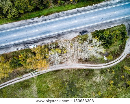 top view of car on asphalt track with colorful trees and rolled road on one side, aerial photo