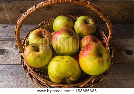 ripe autumn apples in the basket, on wooden background.