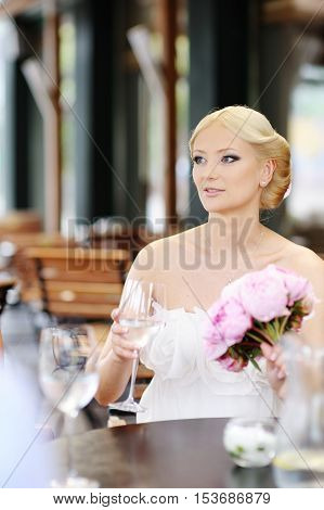 Bride drinking champagne at her wedding on summer day