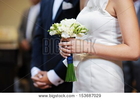 Bride holding flowers at the wedding ceremony in church