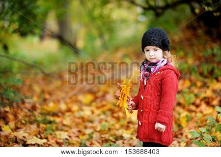 Little Girl In Bright Red Coat At Autumn