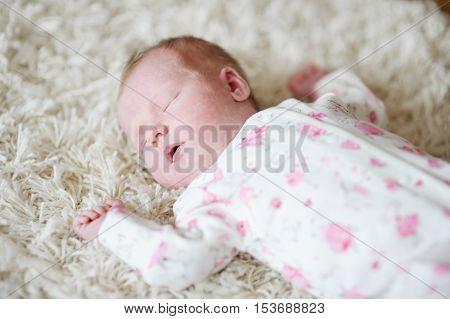 Adorable sleeping newborn baby girl portrait at home