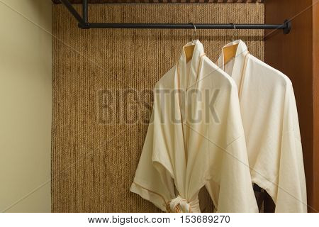 two off white color bathrobes hanging in warmly design closet room for copy space
