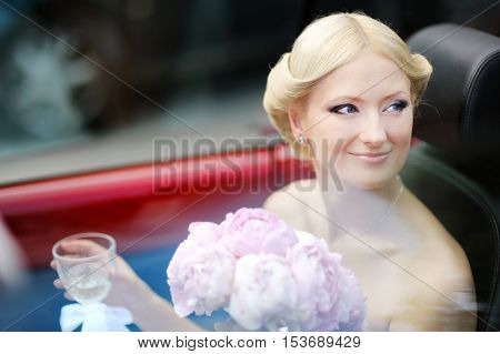 Beautiful young bride portrait in a car on summer day