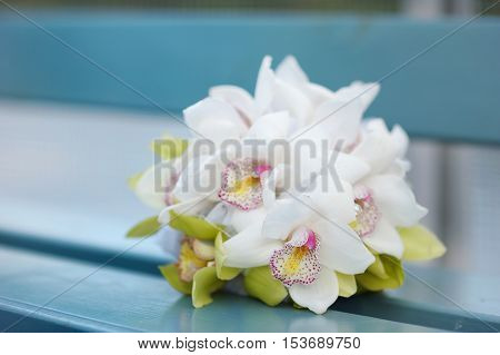 Beautiful white wedding florals on a blue bench
