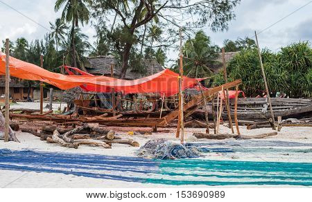 wooden boats and large colorful fishing nets lying on seashore