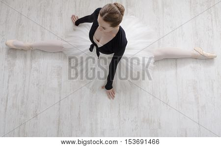 Classical Ballet dancer portrait. Beautiful graceful ballerine in tutu skirt practice split ballet position in class room background. Ballet class training, high-key soft toning. Top view from above