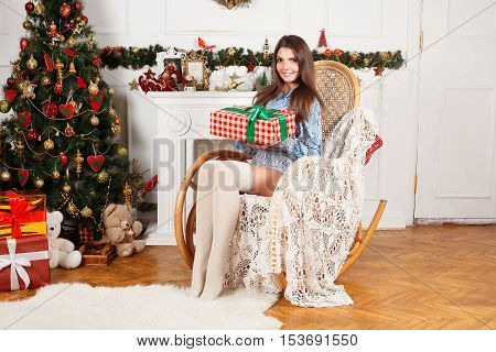 Beautiful girl in a Christmas room with the gift of hands in a rocking chair