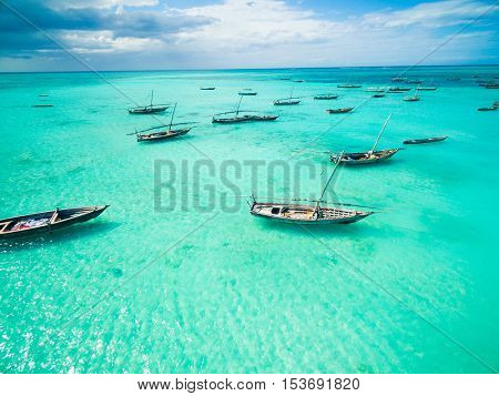 beautiful colorful seascape with african fishing boats in clear ocean, aerial photo