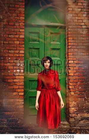 Girl in red retro dress on a background of vintage wooden door. Nostalgic mood. Warm tinted