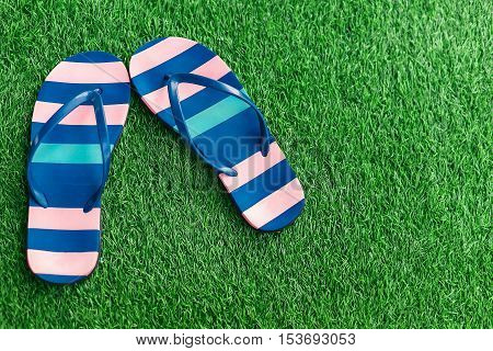 Closeup of bright flip flops on green grass. A bright Sunny day.