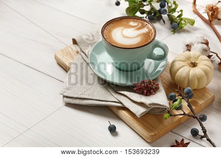Pumpkin spice latte. Blue coffee cup with creamy foam, cinnamon sticks, autumn sloe and small yellow pumpkins at white wood background. Fall hot drinks, cafe and bar concept