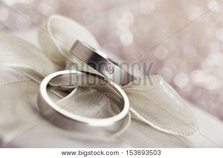 engagement rings on silver bow, with sparkling bokeh in background