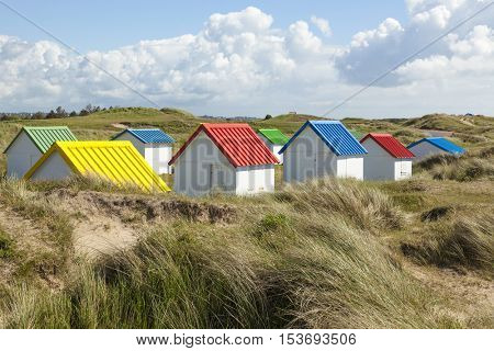 Colorful beach huts in the dunes at Gouville-sur-Mer, Normandy, France