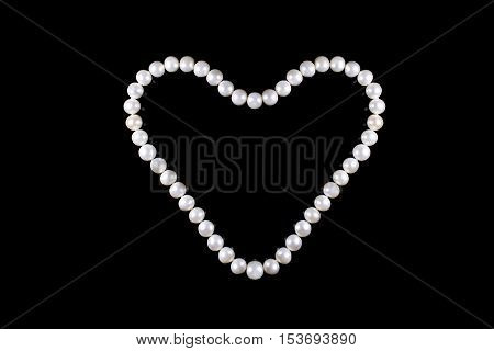 Heart of pearl beads isolated on black background