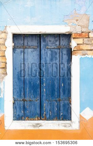 Close up view of the old window with closed blue wooden shutter. Blue and orange plaster is in the background. Vertically.