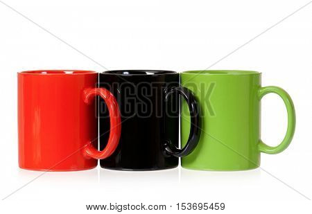 Three color coffee cups - red, green and black, isolated on white background. Set of ceramic motley mugs for tea with clipping path.
