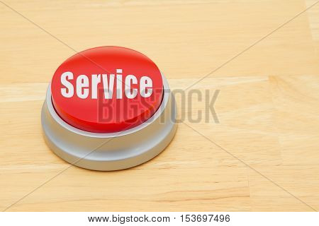 A Service red push button A red and silver push button on a wooden desk with text Service