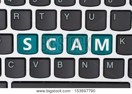 Getting scammed online A close-up of a keyboard with teal highlighted text Scam