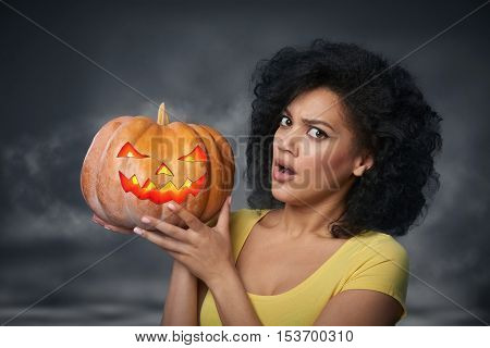 Scared woman holding Halloween pumpkin head jack lantern over smoky background