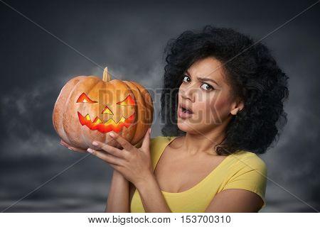 Scared woman holding Halloween pumpkin head jack lantern over smoky background