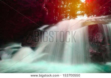 View of waterfall and sunny beams in deep forest at National Park.Vivid color style