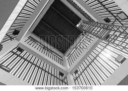 Upside and down view of a old spiral staircase of tower in black and white tonearchitecture abstract.