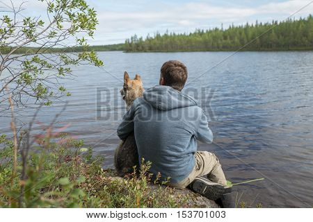 Man and dog are sitting on the lake shore and looking into the distance