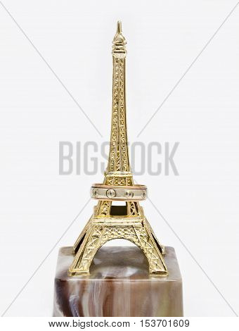 Wedding ring on the statue Eiffel Tower on white background