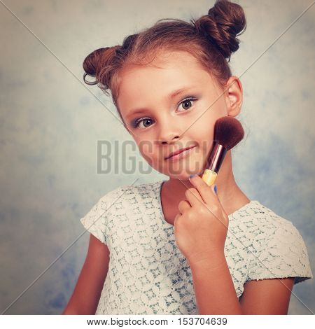 Cute Beautiful Small Kid Girl Applying Tonal Cosmetic On The Face Using Makeup Brush With Happy Smil