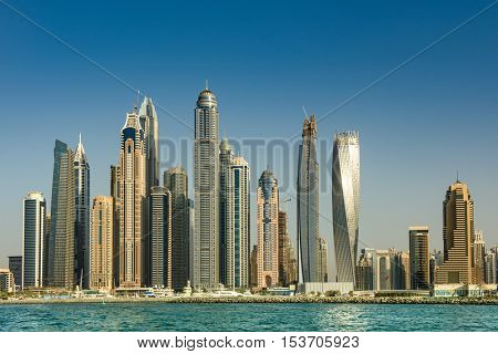 DUBAI, UAE - OCTOBER 09, 2016. View of various skyscrapers including Cayan Tower in Dubai Marina with stunning turquoise waters as foreground