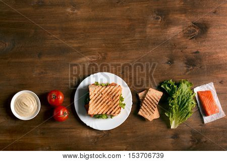 Club sandwich prepared with fish on the wooden board. Top view with copy space
