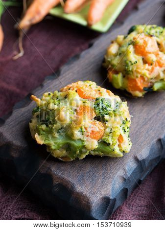 Baked vegetable patties with carrots, broccoli and cheese on dark wooden serving board. Vertical image