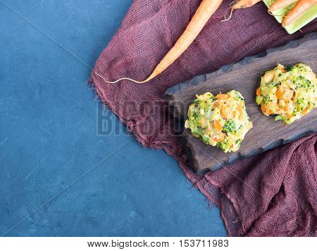 Baked vegetable patties with carrots, broccoli and cheese on dark wooden serving board. Copy space. Top view