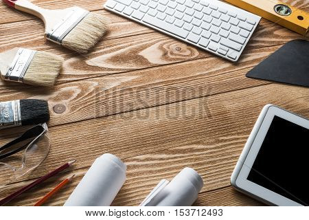Variety of tools of builder and tablet pc on wooden texture table