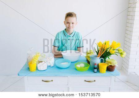 Boy preparing dough in the kitchen, breakfast
